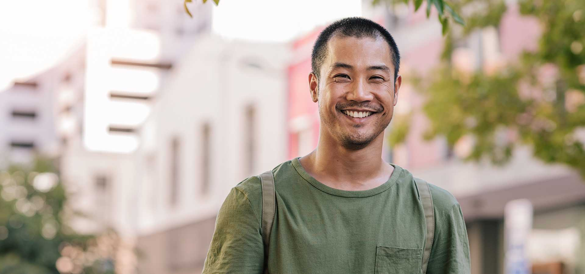 Portrait of a casually dressed young Asian man smiling while standing outside on a city street.