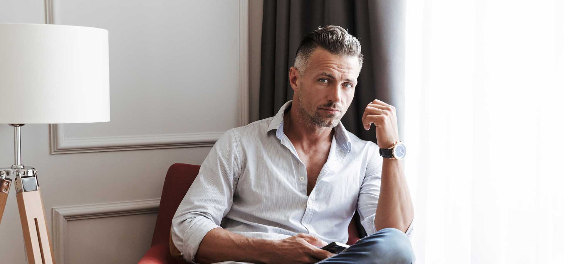 Photo of caucasian handsome man 30s in casual wear using smartphone while sitting in armchair in living room or hotel apartment.