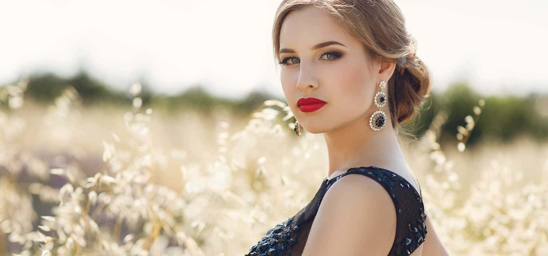 Brown-eyed brunette with bright red lipstick on her lips, stylish makeup, elegant fashionable hair style in the ears wearing earrings,wearing a black dress,posing in a meadow outside the city in the summer outdoors.