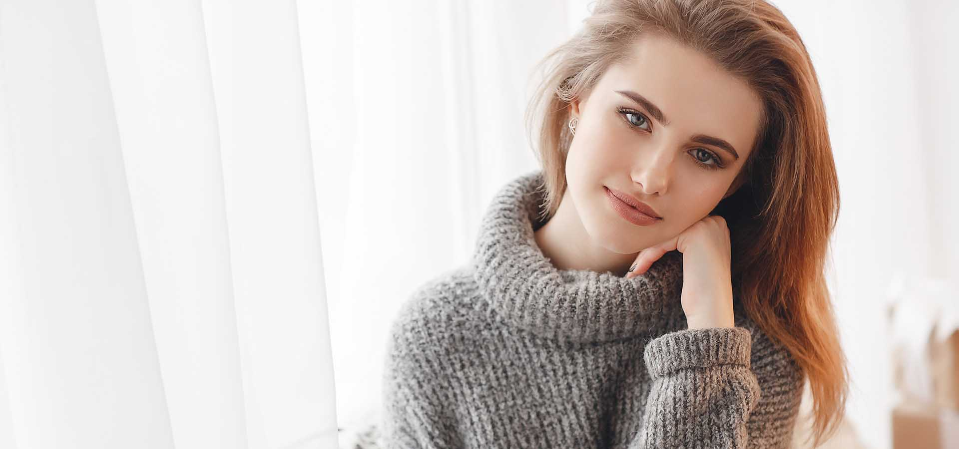 Beautiful sexy girl in an elegant gray sweater. Close-up, portrait of a woman, model, indoors.