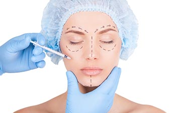 Beautiful young shirtless woman in medical headwear and sketches on face keeping eyes closed while doctors hand making an injection in face