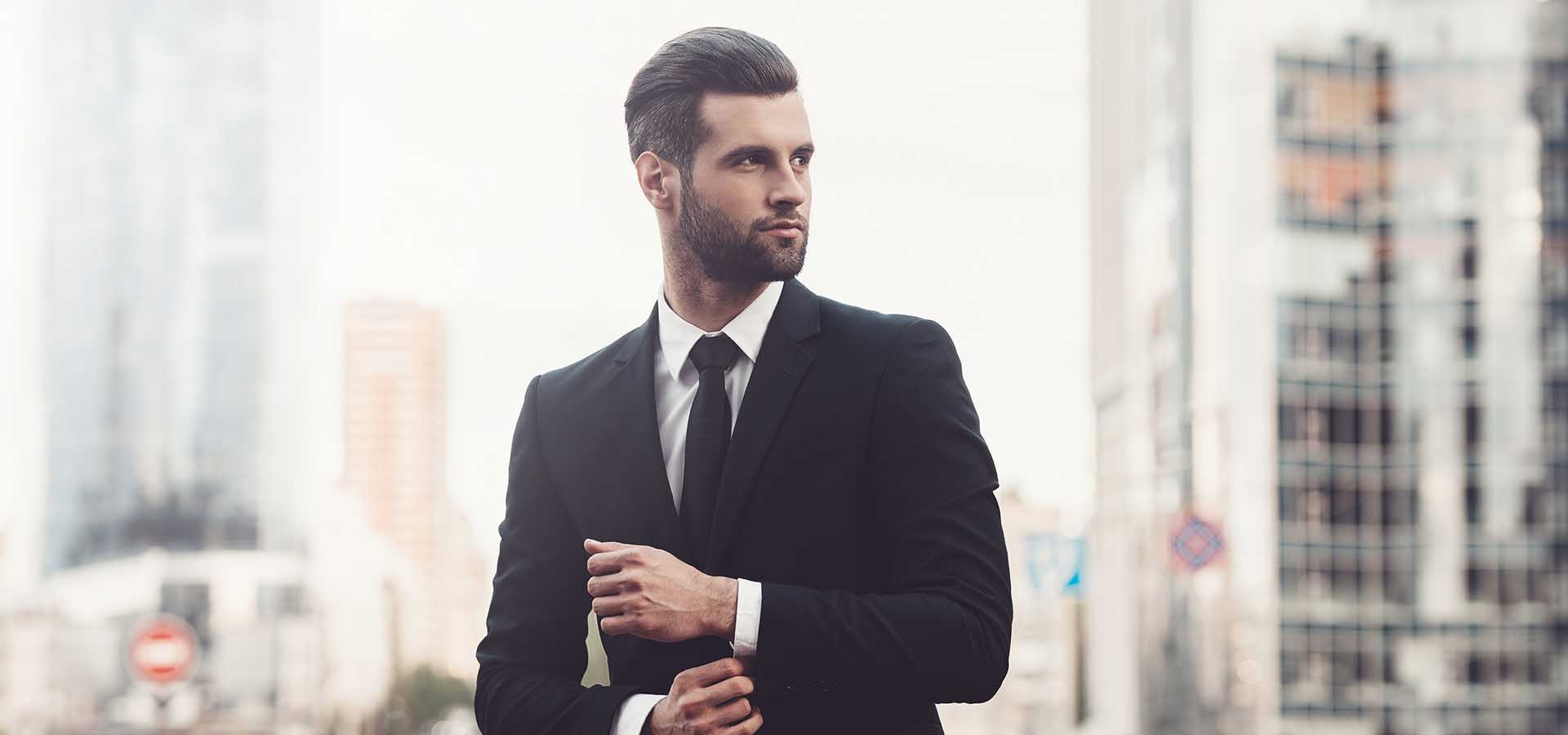 Modern businessman. Confident young man in full suit adjusting his sleeve and looking away while standing outdoors with cityscape in the background.