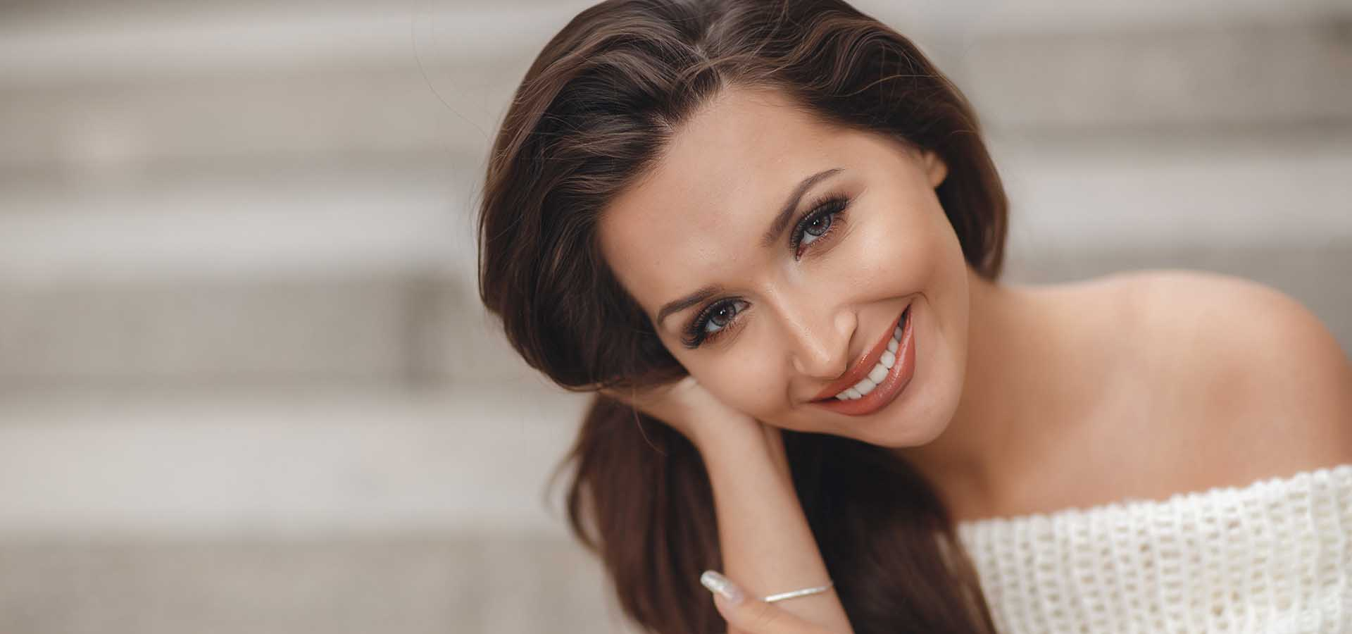 Bright portrait of beautiful brunette woman with long straight hair, long eyelashes, grey eyes, light makeup, nice smile, white straight teeth, posing sitting outdoors on one of the streets in the spring.