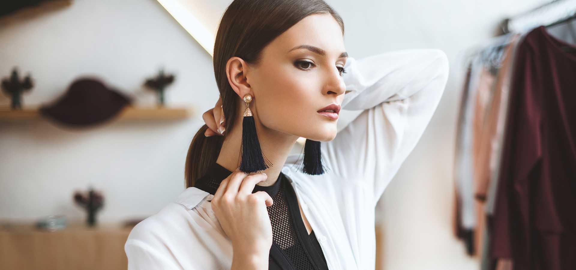 Elegant, beautiful, fashionable woman choosing earrings in boutique.