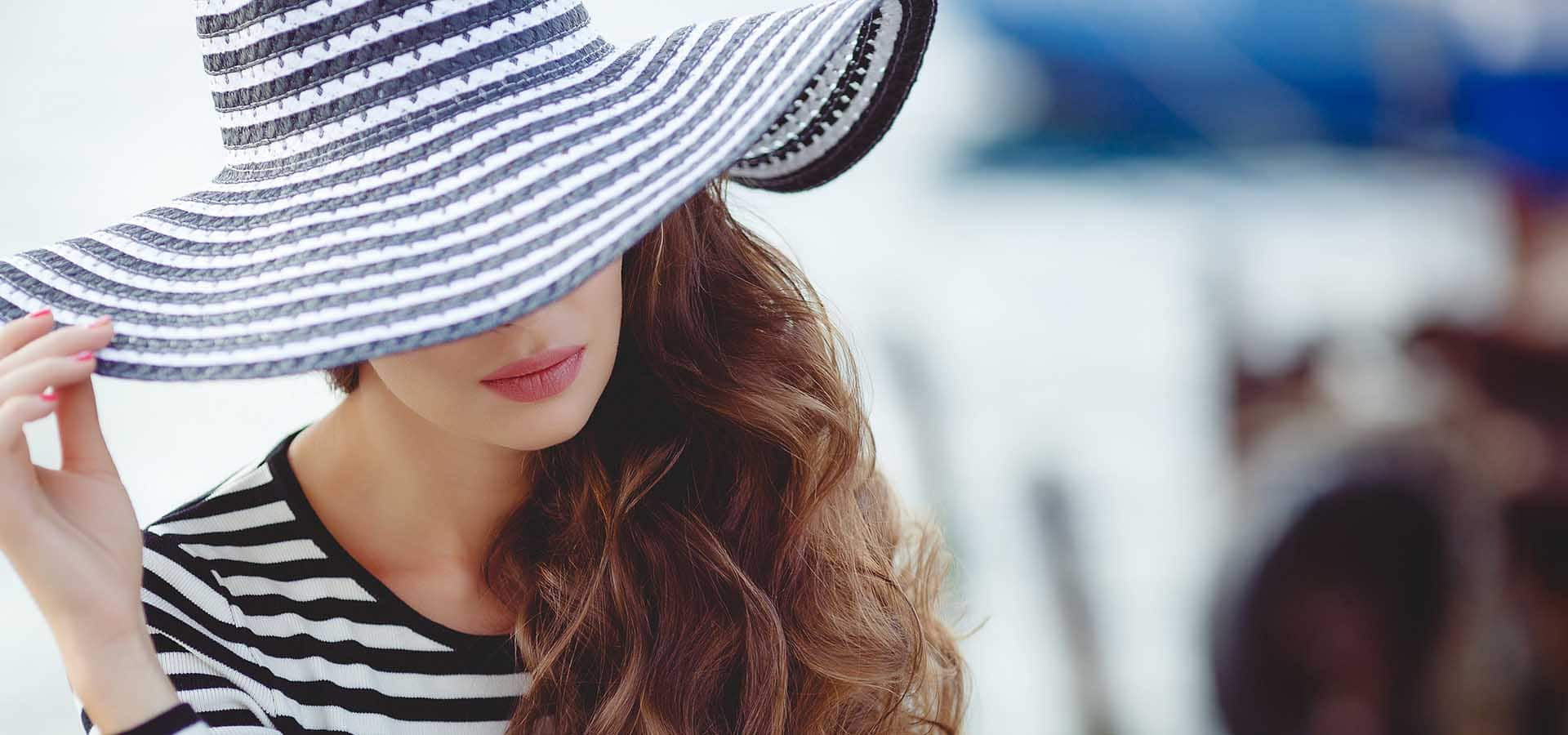 Beautiful young woman model looks, brunette with long curly hair, on his head wearing striped straw hat with a large brim pulled down to his eyes, dressed in a striped summer dress.