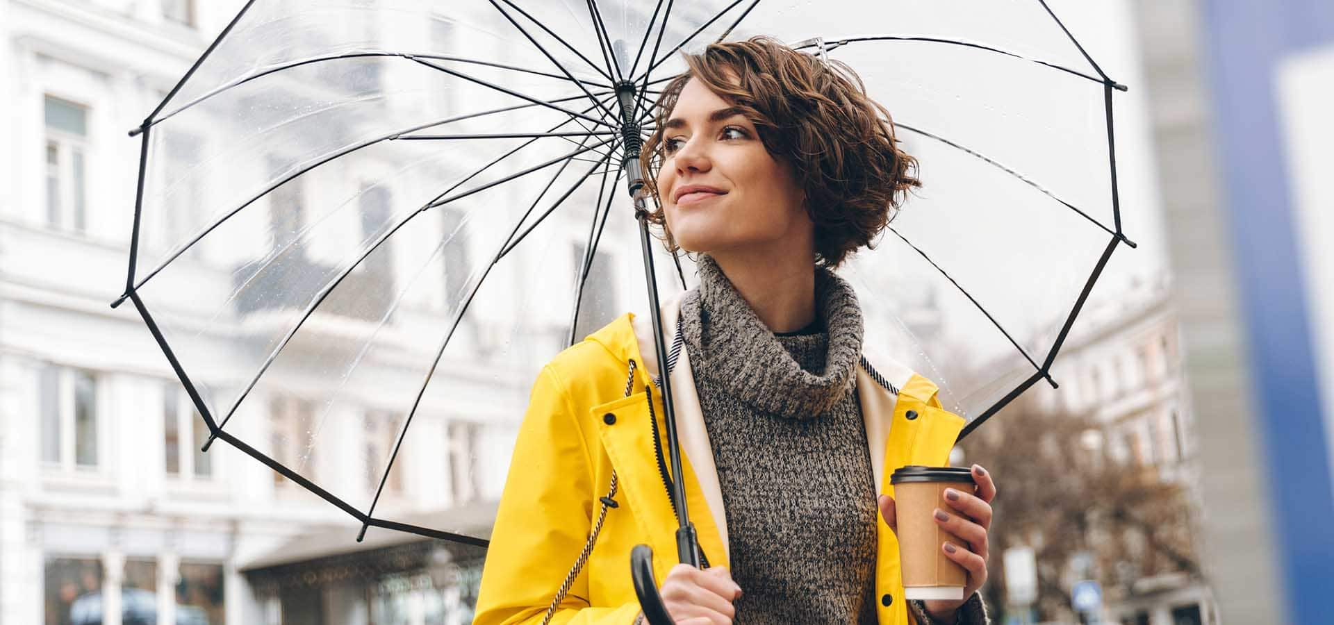Stylish woman in yellow raincoat walking through urban area under big transparent umbrella, holding takeaway coffee in hand.