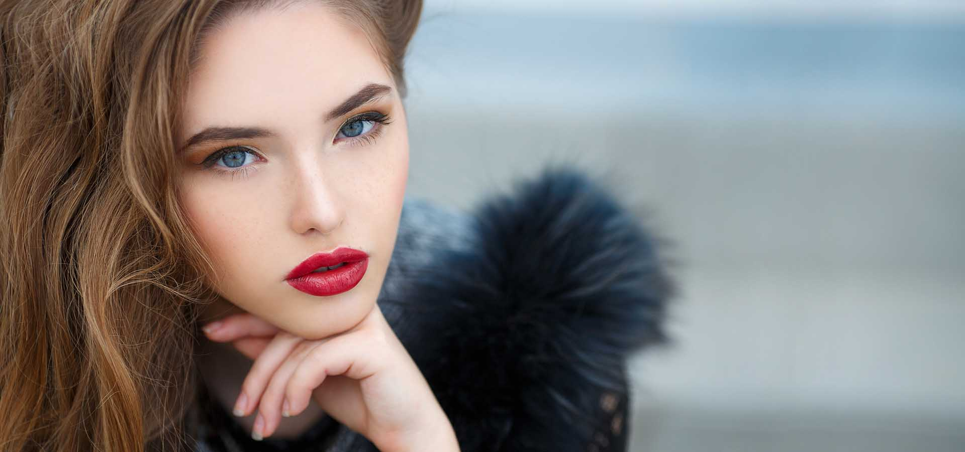 Portrait of beautiful young woman model with long blond curly hair and gray eyes, light makeup and red lipstick, dressed in fur jacket, autumn photo shoot on the background of blurred city streets.