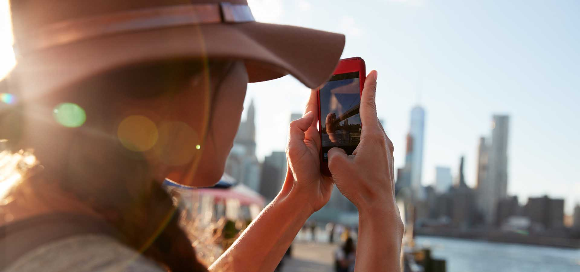 Woman taking photo of Manhattan skyline on mobile phone.